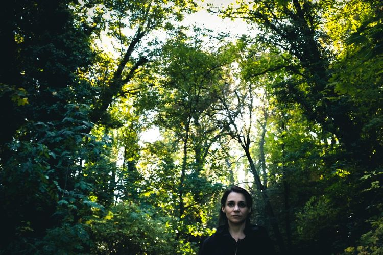 Portrait of woman against trees in forest