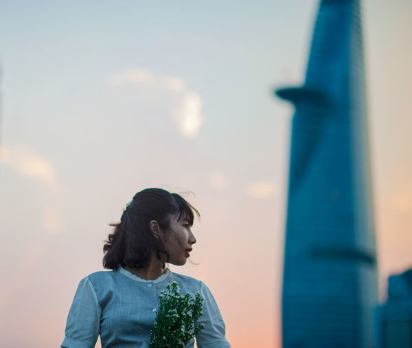 Young woman standing against sky during sunset