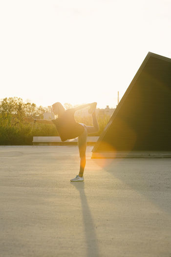 Sporty fit girl doing yoga pose of a swallow during sunset Yoga Pose Architecture Balance Bright Built Structure Day Effort Exercising Full Length Healthy Lifestyle Leisure Activity Lens Flare Lifestyles Nature One Person Outdoors Real People Sky Sport Sunlight Sunset Women Yoga Practice