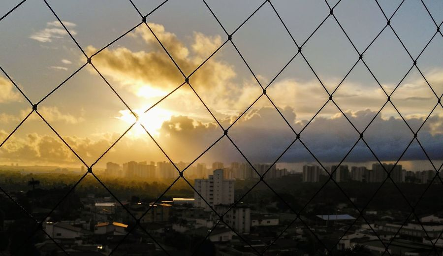 behind a net, the sun is partially covered by stormy clouds Sunrise Stormy Clouds Early Morning Buildings Skyline Sunset Business Business Finance And Industry City Protection Metal Security Chainlink Fence Sky Wire Mesh Idyllic Scenics Silhouette Razor Wire Fence Tranquil Scene Calm Shore Non-urban Scene