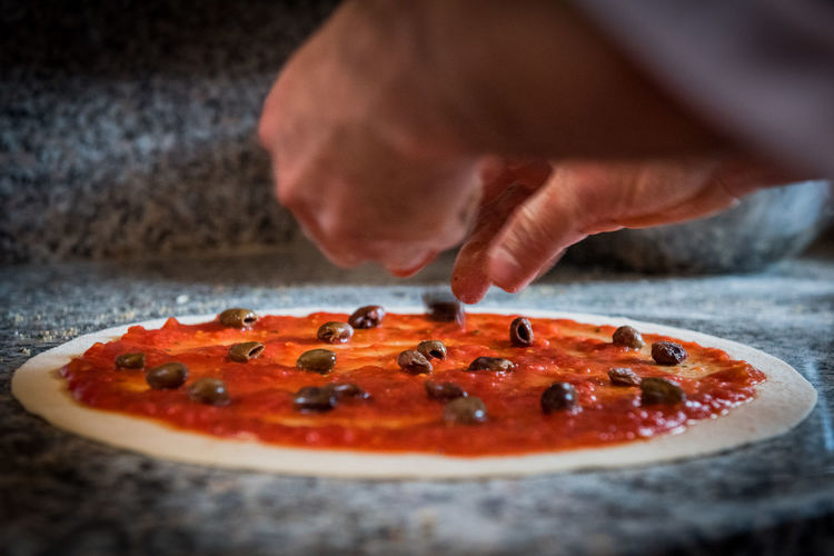 Cropped Image Of Hands Making Pizza On Table