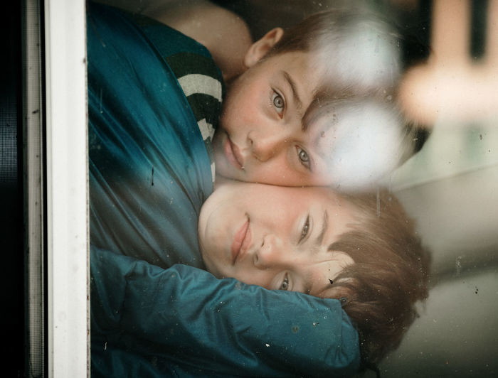 Portrait of brothers embracing seen through window