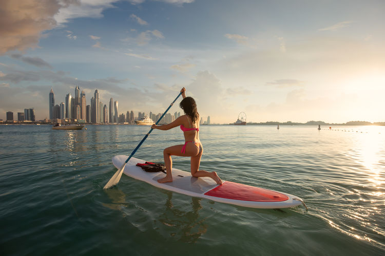 Beautiful girl in bikini paddles on a surfboard in front of the skyline from Dubai Marina Water Sky One Person Waterfront Nautical Vessel Transportation Leisure Activity Lifestyles Sea Architecture City Nature Cloud - Sky Built Structure Building Exterior Sport Outdoors Office Building Exterior Sup Paddleboat Dubai UAE Travel Hoiday Sunset