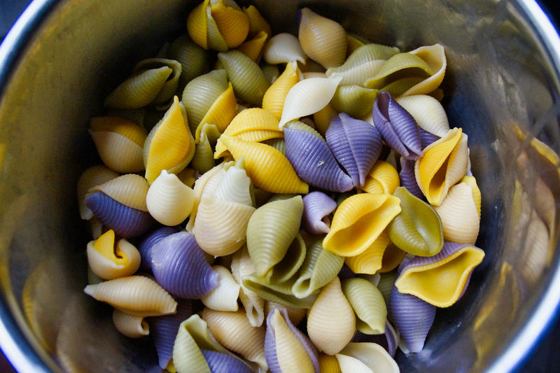 High angle view of multi colored conchiglie pastas in container