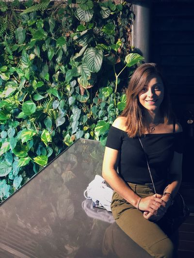 Portrait Of Smiling Young Woman Sitting Against Plants