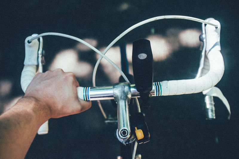 Cropped image of man holding bicycle handlebar on road