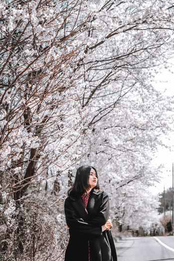 Full length of woman standing by cherry tree in winter
