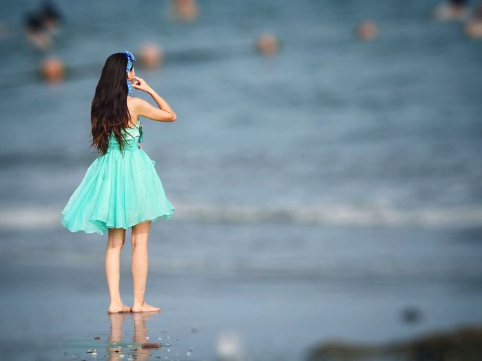 Rear view of woman standing on wet shore