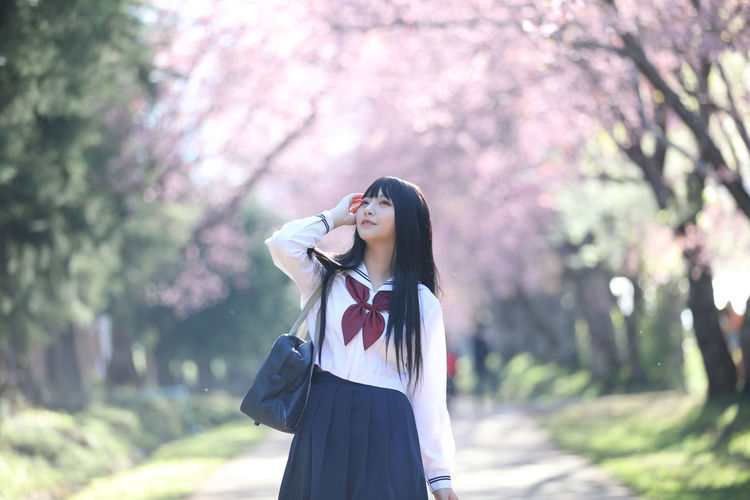Young woman looking away while standing against cherry tree