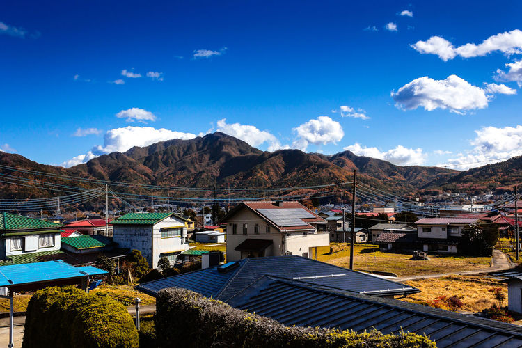 EyeEmNewHere Japan Travel Beauty In Nature Blue Built Structure City Cloud - Sky Day Environment High Angle View House Mountain Mountain Peak Mountain Range Nature No People Outdoors Residential District Sky Sunlight TOWNSCAPE Travel Destinations