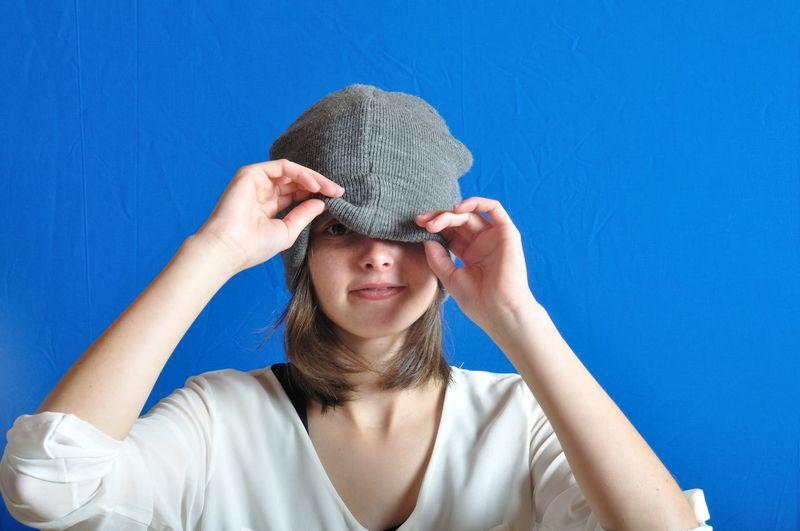 Portrait of woman wearing hat against blue background
