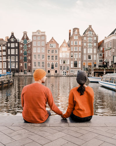 Rear view of couple sitting by canal against buildings in city