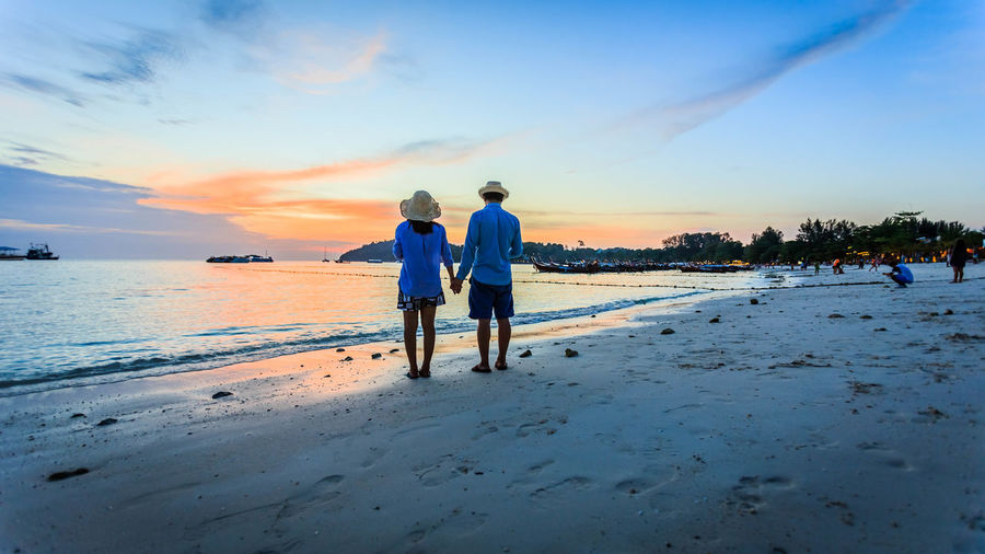 Rear view of couple standing at beach against sky during sunset