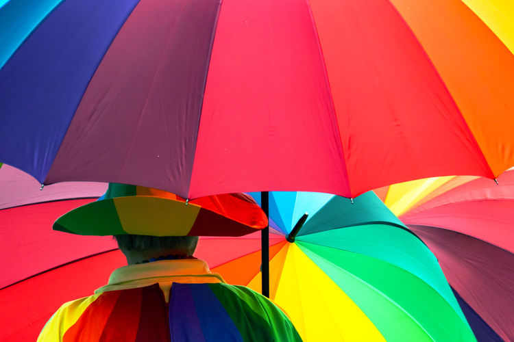 Rear view of man with colorful umbrellas while standing outdoors