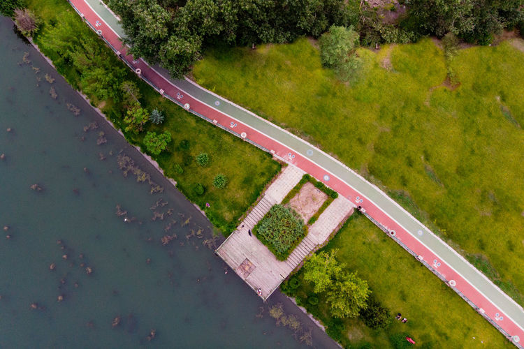Top view of nice pier at the riverside. Plant Tree Day High Angle View Nature Green Color Water No People Outdoors Grass Growth Beauty In Nature Transportation Architecture Road Pool Reflection Land Footpath Riverside Cycling Path Walking Path Top View Dronephotography Aerial View