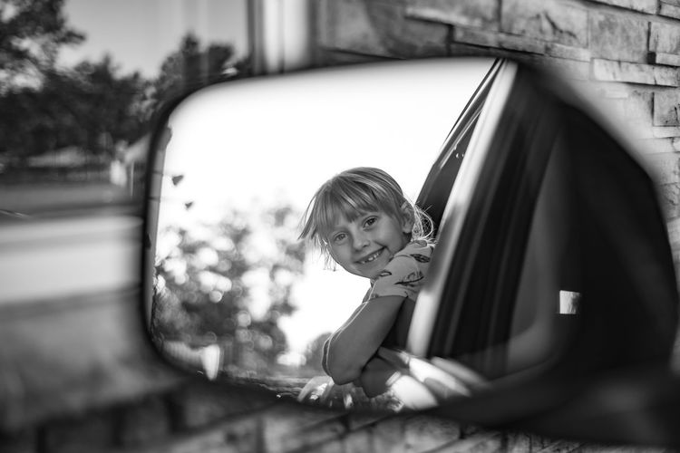 Portrait Of Cheerful Girl Leaning Out From Car Window Seen In Side-View Mirror