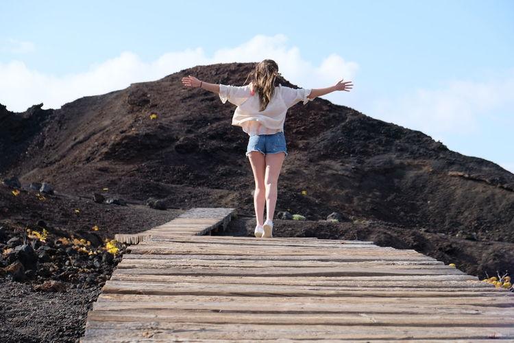 Full length of woman walking on boardwalk against mountain