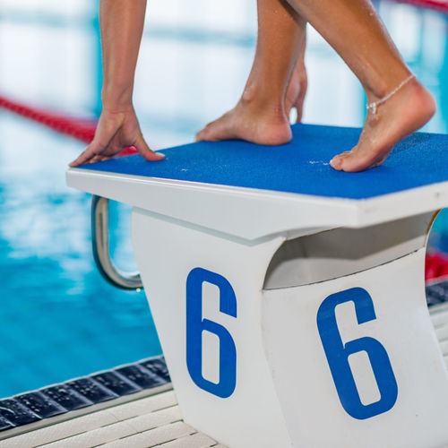 Low section of female swimmer on diving platform at poolside