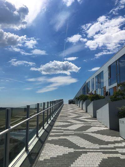 Empty footpath by buildings against sky