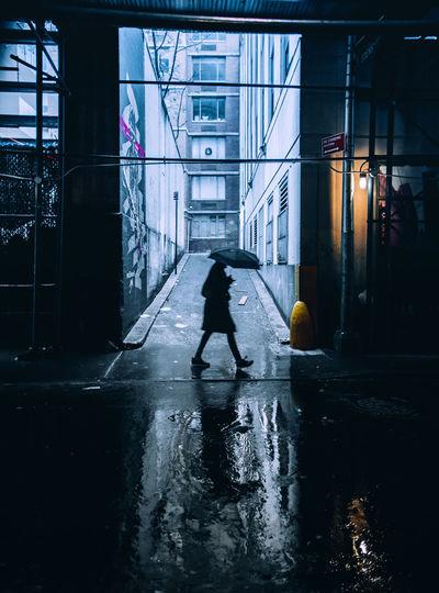 Woman walking on wet street amidst buildings in city