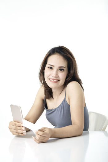 Asian woman shopping online studio shot on white background, for online shopping, technology and internet concept, Thai Studio Shot 30-34 Years Shopping Online  Young Female Happy Asian  Laptop Beautiful Internet Attractive Smile person Computer People Portrait Holding Phone Beauty Mobile Pretty Technology Payment Adult Using Lifestyle Cheerful Purchase Business Wireless Lady Chinese Fashion Looking Smartphone Japanese  Korean Credit Card Empty Text Copy Space Looking At Camera Wireless Technology One Person White Background Smiling Communication Front View Indoors  Young Women Young Adult Sitting Connection Casual Clothing Women Hair Beautiful Woman Hairstyle