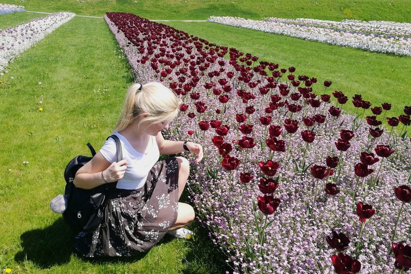Woman Sitting By Flowering Plants