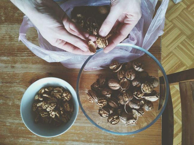 Decorticating walnuts on wooden table. Human Hand High Angle View Human Body Part One Person Table Indoors  Decorticate Walnut Walnut Shell Walnuts Crack Cracked Cracking Open Decorticating