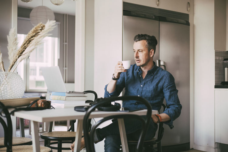 Man looking at camera while sitting on table at home