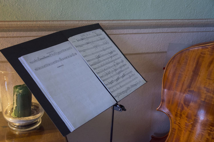 High angle view of sheet music and cello against wall