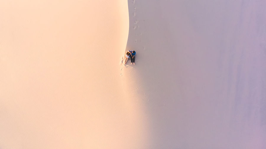 High angle view of couple sitting on sand at desert