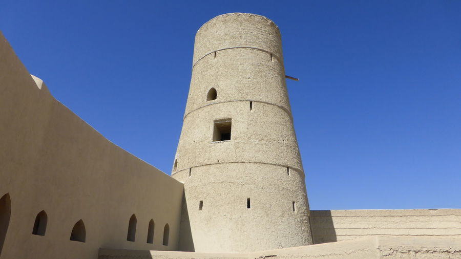 Low angle view of tower at bahla fort against clear sky