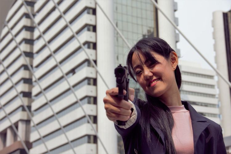 Close-up of woman pointing pistol at camera