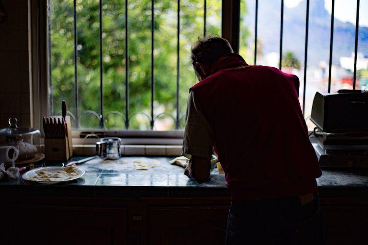 Rear view of man preparing food by window in kitchen