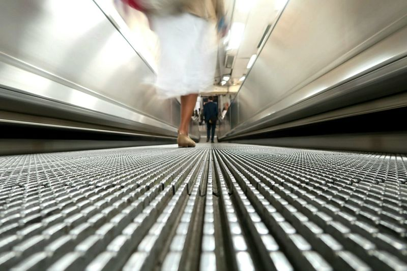 One Person Motion Full Length The Way Forward Modern Indoors  Low Section Technology Woman Walking Pedestrian Travelator Station Transport Transportation London Underground Commuters Low Angle View Low Perspective Leading Lines Metal Metallic EyeEm LOST IN London Perspectives On People