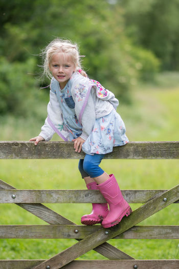 Portrait of cute girl climbing on wooden fence