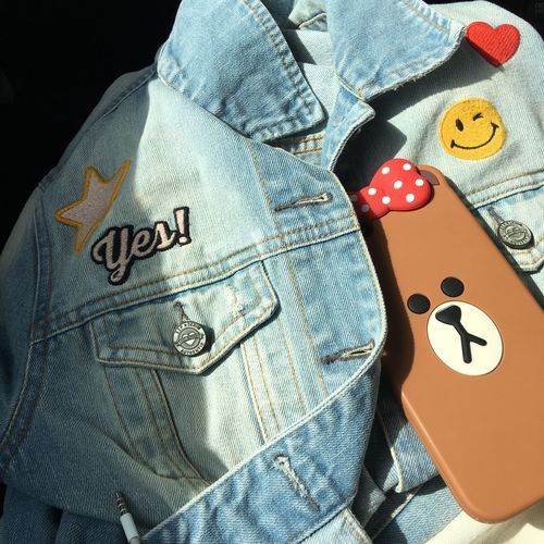 High angle view of mobile phone on denim jacket