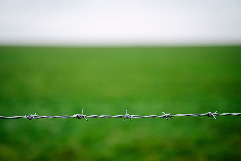 Barbed wire fence on field