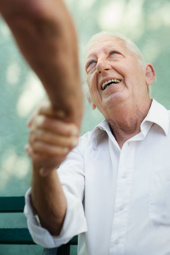 Senior man shaking hands with friend while sitting outdoors