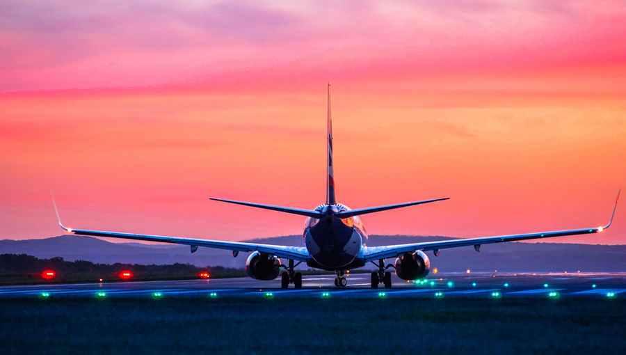 Airplane at airport runway during sunset