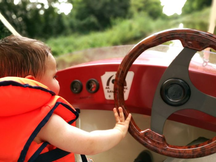 Boy Touching Steering Wheel While Travelling In Boat