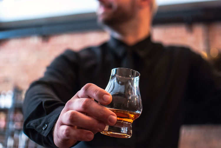 Midsection Of Man Holding Whiskey Glass In Bar