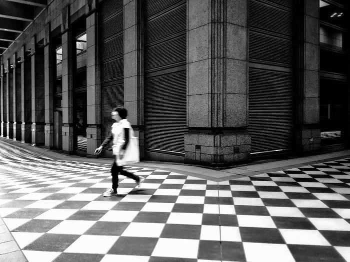 Rear view of woman walking on tiled floor in building