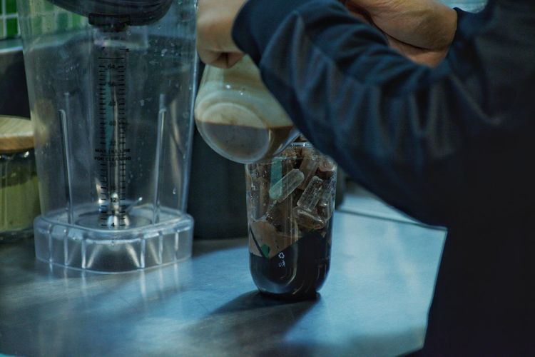 Midsection of person preparing drink in glass table