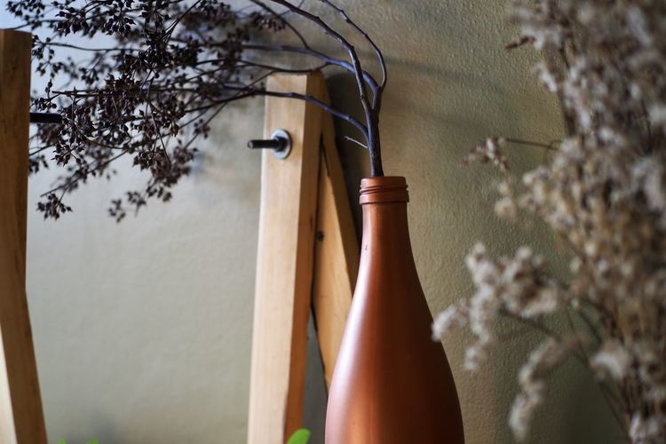 Close-up of flower vase against wall