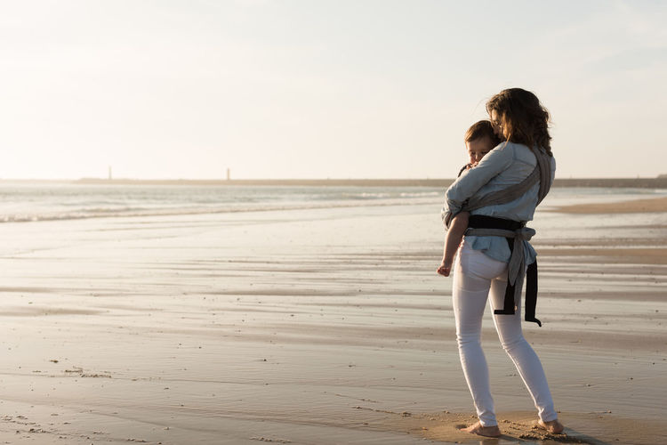 Mother carrying son while walking at beach