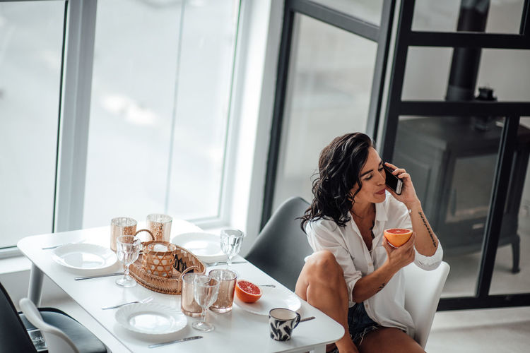 Woman eating fruit while talking over smart phone while sitting on chair at home