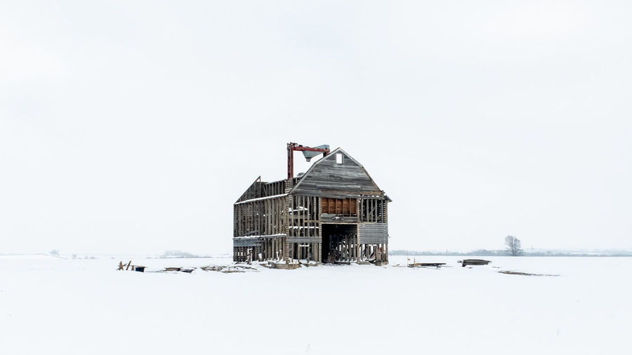 Building on snow covered land against clear sky
