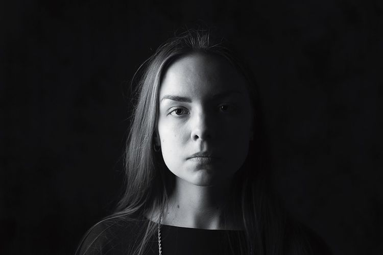 Close-up portrait of beautiful young woman over black background