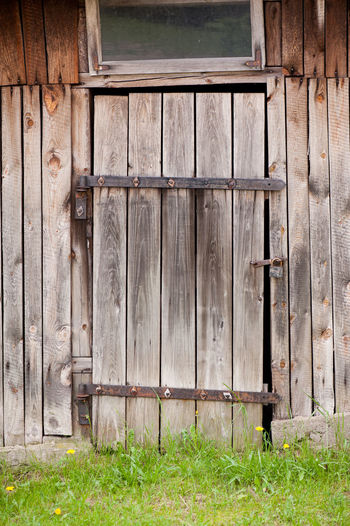 Architecture detail of wood old shed dilapidated cubby door and padlock, damaged building in Poland. Private abandoned construction of boards fall to ruin. Vertical orientation, nobody. Abandoned Architecture Boards Broken Building Crevice Cubby Door Doorframe Entrance Fissure Hut Lock Lumber No People Old Padlock Plank Planks Shack Shed Timber Weathered Wood Wooden