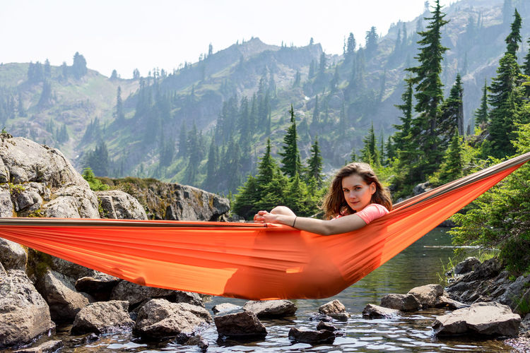 Young man sitting on hammock against trees on mountains